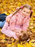 Kids in autumn orange leaves. Stock Image