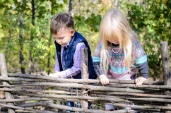 Kids in Autumn Outfit Playing at the Wooden Fence Stock Photo