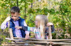 Kids in Autumn Outfit Playing at the Wooden Fence Stock Images