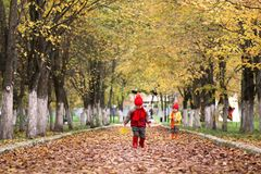 Kids in autumn park with pumpkin. Around fall leaves Stock Photo