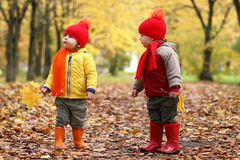 Kids in autumn park with pumpkin. Around fall leaves Royalty Free Stock Photos