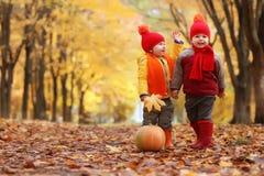 Kids in autumn park with pumpkin Stock Photo