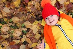 Kids in autumn park with pumpkin. Around fall leaves Stock Photos