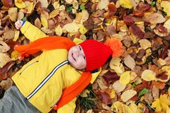 Kids in autumn park with pumpkin. Around fall leaves Royalty Free Stock Photo