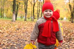 Kids in autumn park with pumpkin. Around fall leaves Stock Image