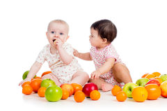 Kids babies eating healthy food fruits. Funny kids babies eating healthy food fruits on white background Royalty Free Stock Photos