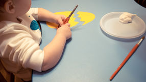 Kids baby boy`s blue school developing lesson sits and mixes paint yellow and white tassel royalty free stock photo