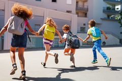 Kids with backpacks run to school. Group of kids run together holding hands and wearing backpacks toward school Royalty Free Stock Photography