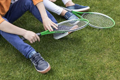 Kids with badminton rackets sitting on green lawn Stock Photos