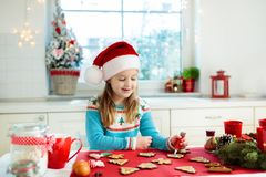 Kids bake Christmas cookies. Child in Santa hat cooking, decorating gingerbread man for Xmas celebration. Family preparing sweets stock photos