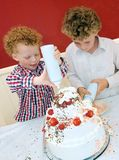 Kids Baking Cake. Two boys having fun decorating a huge cake with whipped cream and strawberries(8 and 3 years old royalty free stock photos