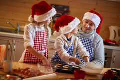Kids baking cookies with father on Christmas Stock Photos