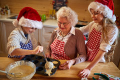 Kids baking cookies with grandmother on Christmas Royalty Free Stock Photos