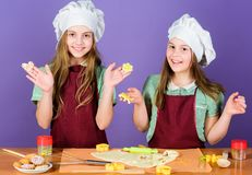 Kids baking cookies together. Kids aprons and chef hats cooking. Family recipe. Culinary education. Mothers day. Baking. Ginger cookies. Girls sisters having royalty free stock photo