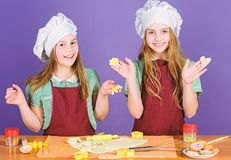 Kids baking cookies together. Kids aprons and chef hats cooking. Family recipe. Culinary education. Mothers day. Baking. Ginger cookies. Girls sisters having stock image