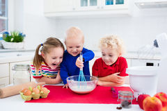 Kids baking a pie in white kitchen. Cute kids, adorable little girl, boy and funny baby making dough for a cake. Children mix flour, eggs and milk baking apple Stock Photos