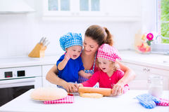 Kids baking in a white kitchen. Kids and mother baking. Two children and parent cooking. Little girl and baby boy cook and bake in a white kitchen with modern Royalty Free Stock Images