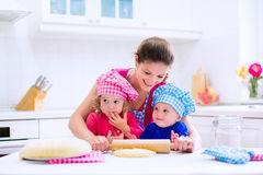 Kids baking in a white kitchen. Kids and mother baking. Two children and parent cooking. Little girl and baby boy cook and bake in a white kitchen with modern Stock Photography