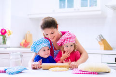 Kids baking in a white kitchen. Kids and mother baking. Two children and parent cooking. Little girl and baby boy cook and bake in a white kitchen with modern stock photos