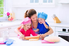 Kids baking in a white kitchen. Kids and mother baking. Two children and parent cooking. Little girl and baby boy cook and bake in a white kitchen with modern Royalty Free Stock Photos