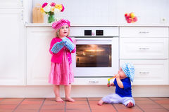 Kids baking in a white kitchen. Kids baking. Two children cooking. Little girl and baby boy cook and bake in a white kitchen with modern oven. Brother and sister Stock Photo