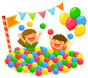 Kids in a ball pit. Two kids playing in a ball pit with a festive atmosphere Royalty Free Stock Image