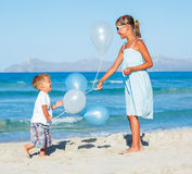 Kids with ballons on the beach Stock Photos