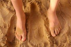 Kids bare feet on sand close up photo. On sunny beach Royalty Free Stock Photo