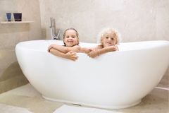 Kids in bath. Children bathing. Family bathroom. Kids taking bubble bath. Children bathing in freestanding bathtub. Little boy and girl playing with water royalty free stock photo