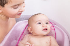 Kids Bath Time. Pretty baby girl is having a bath in her bathtub with her, brother Stock Images