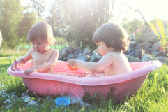 Kids in bath water outdoor Royalty Free Stock Image