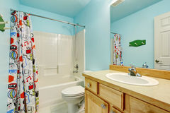 Kids bathroom in blue tones with wooden cabinets and colorful shower curtain. Stock Image