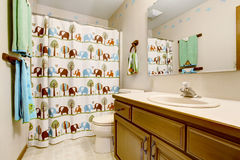 Kids bathroom interior with animal patterned curtain and green and blue towels. Stock Photos