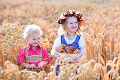 Kids in Bavarian costumes in wheat field Stock Photo