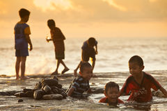 Kids on the beach. Kids playing by the sea in tanah lot bali Stock Photo
