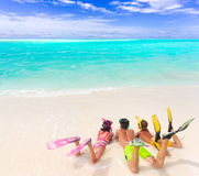 Kids on beach with dive gear. Three sibling children in bathing suits laying on the beach wearing flippers and snorkels by the water stock image