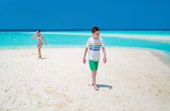 Kids at beach. Little kids on a tropical beach during summer vacation stock photo
