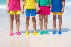 Kids beach shoes. Children summer sea footwear. Kids beach shoes. Colorful footwear for boy or girl. Group of children wearing aqua shoe playing on tropical royalty free stock photo