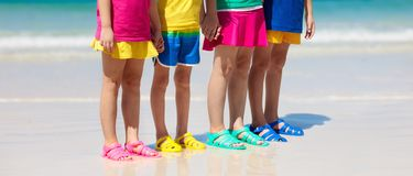 Kids beach shoes. Children summer sea footwear. Kids beach shoes. Colorful footwear for boy or girl. Group of children wearing aqua shoe playing on tropical stock photo