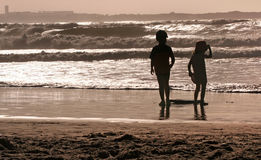 Kids Beach Silhouettes. Kids silhouettes playing on the beach at sunset royalty free stock photography