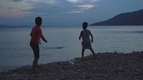 Kids On The Beach Skipping Stones. Two Young Boys Playing Together, Skipping Stones In Slow Motion By The Calm Blue Sea At Sunset stock video