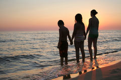 Kids Beach Sunset Horizontal. Silhouette of children holding hands at the beach at sunset. Horizontal format Royalty Free Stock Photo