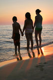 Kids Beach Sunset Vertical. Silhouette of children holding hands at the beach at sunset. Vertical format Stock Images