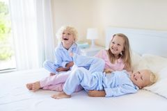 Kids in bed. Children in pajamas. Family bedroom. Royalty Free Stock Images