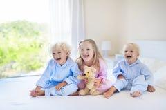 Kids in bed. Children in pajamas. Family bedroom. Stock Image