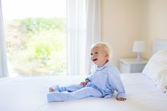 Kids in bed. Children in pajamas. Family bedroom. Royalty Free Stock Photography