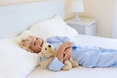 Kids in bed. Children in pajamas. Family bedroom. Stock Images