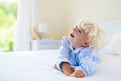Kids in bed. Children in pajamas. Family bedroom. Kids playing in parents bed. Children wake up in sunny white bedroom. Little boy in blue pajamas. Sleepwear stock photography