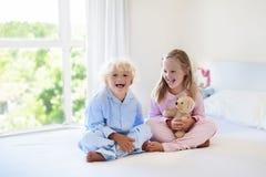 Kids in bed. Children in pajamas. Family bedroom. Stock Photo