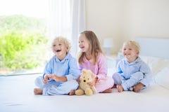 Kids in bed. Children in pajamas. Family bedroom. Royalty Free Stock Photo